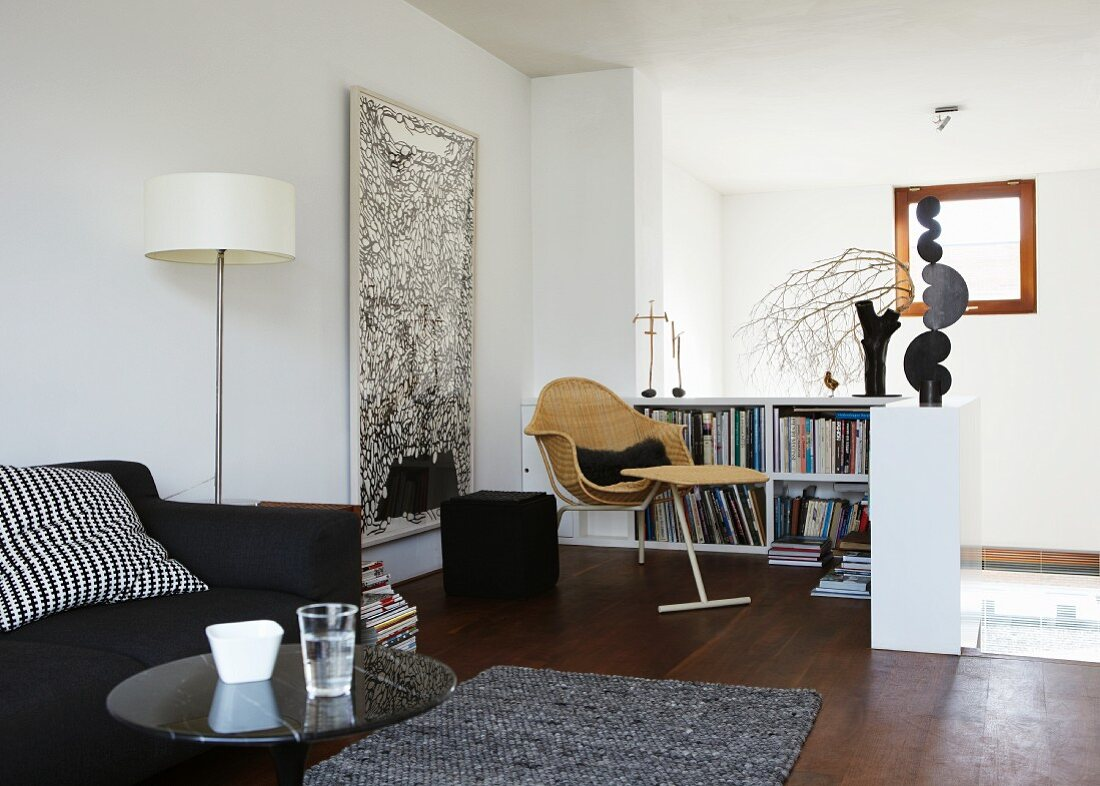 Upholstered sofa and small reading corner with half-height bookcase and Delta armchair in living room