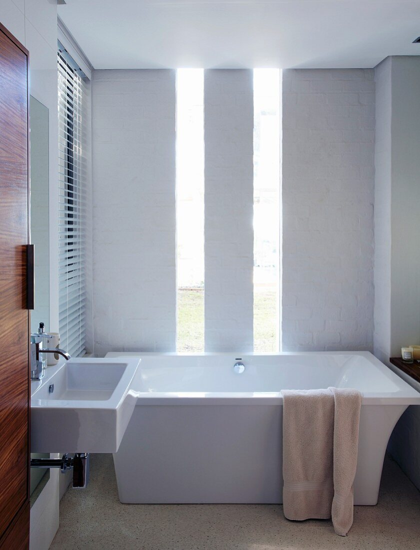 Elegant, minimalist bathroom with exotic wood door and vertical window strips behind free-standing, designer bathtub