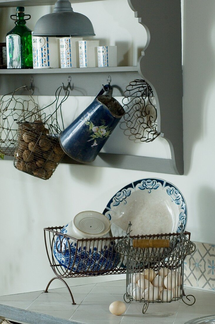 Old wire baskets and vintage metal jug hanging from grey, nostalgic kitchen wall rack; antique crockery in draining rack in foreground