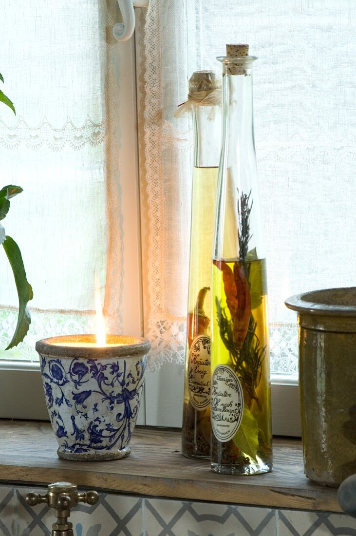 Flavoured oils in labelled bottles next to lit candle