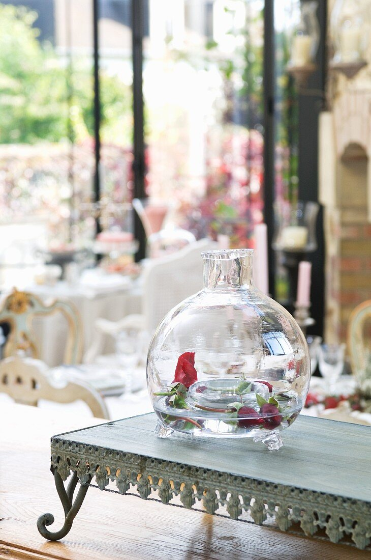 Rosebuds in decorative, hand-blown glass vase