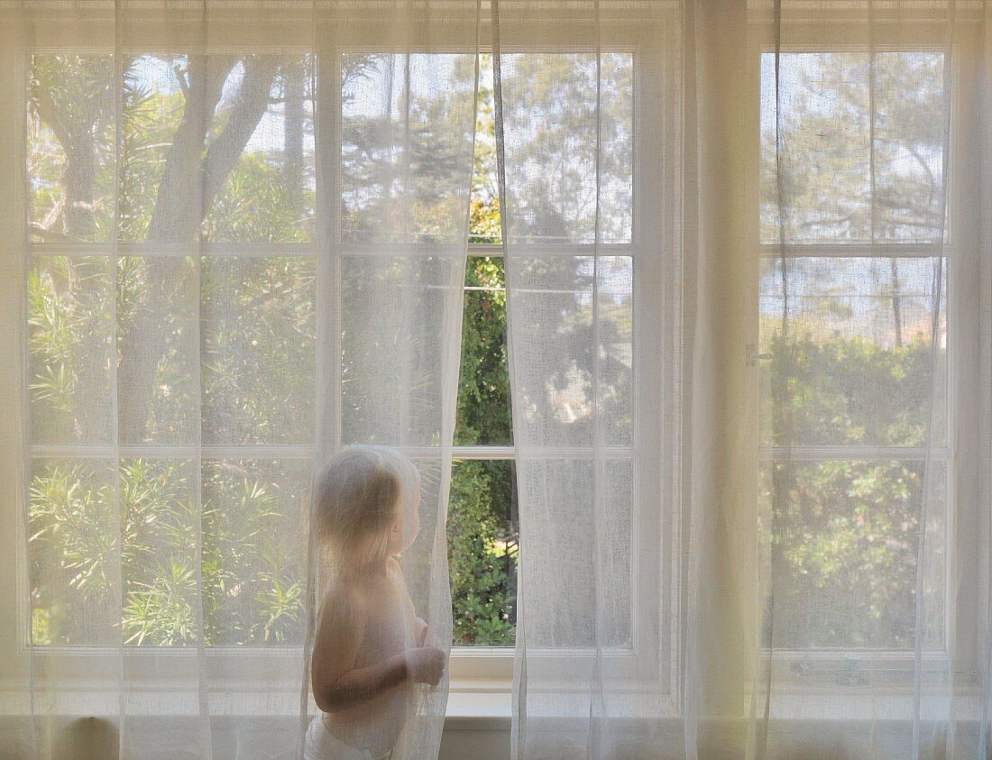 Toddler wearing nappy standing behind curtains at the window