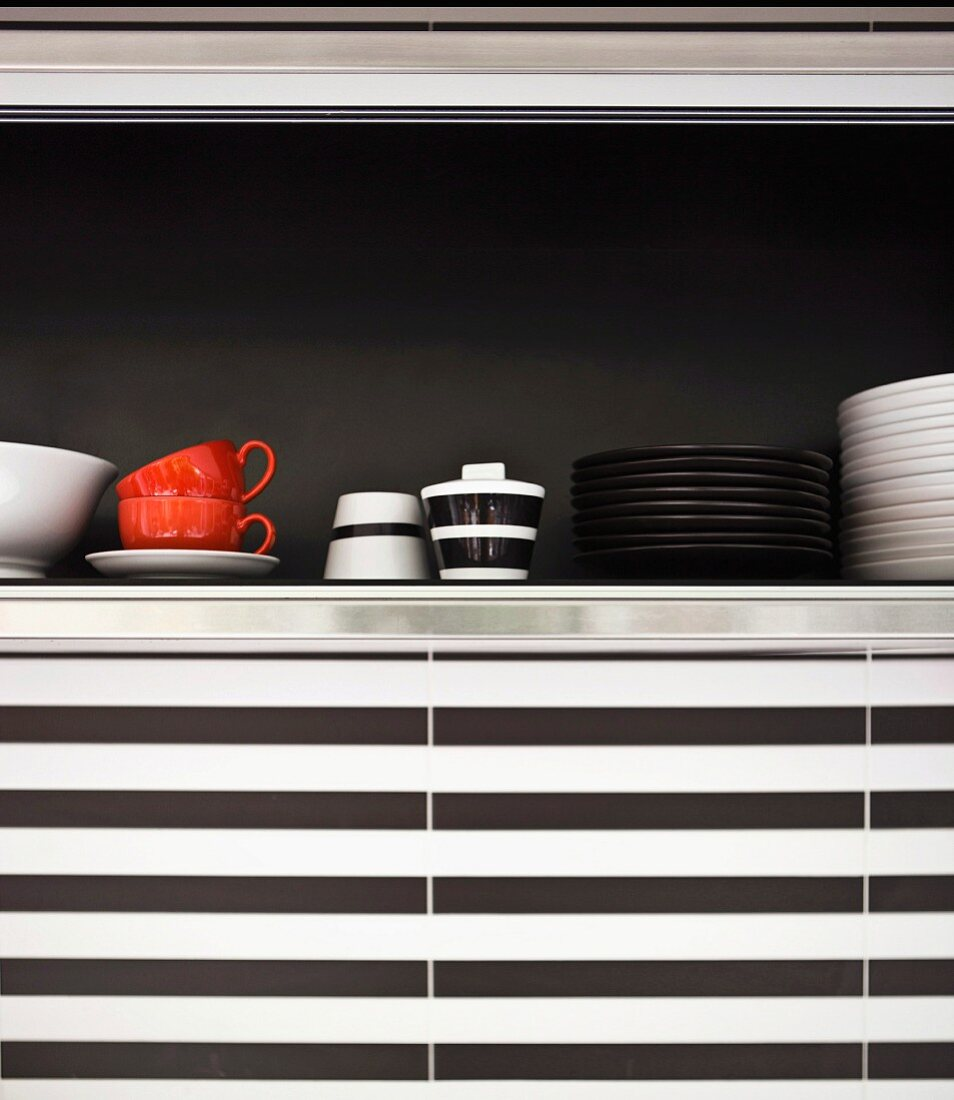 Detail of crockery in wall cupboard with black rear wall and black and white horizontal stripes on kitchen wall