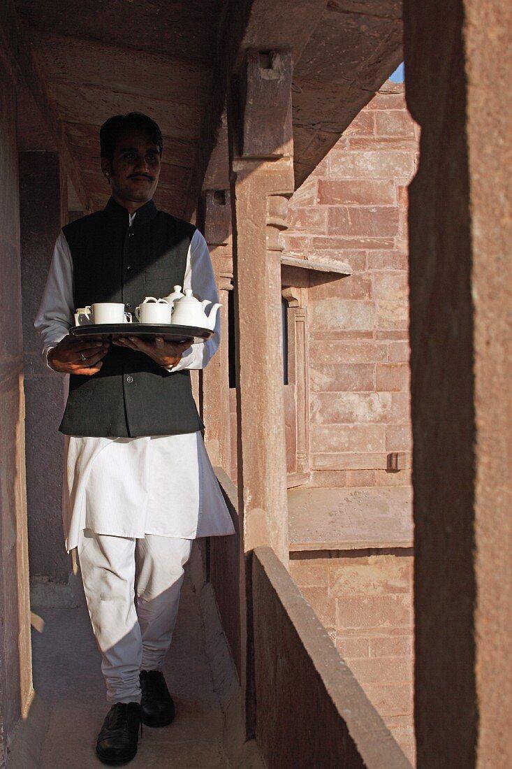Indian waiter serving tea in Raas Haveli Hotel, Jodhpur, India