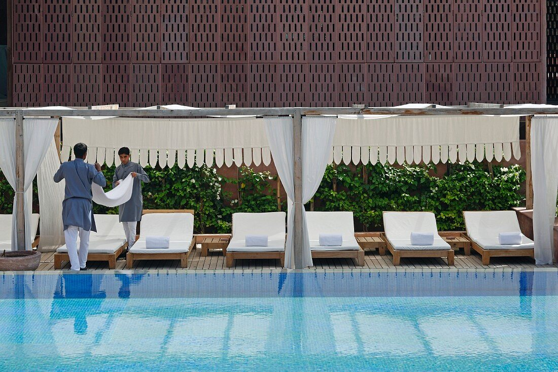 Hotel staff working next to luxurious swimming pool in Raas Haveli Hotel, Jodhpur, India