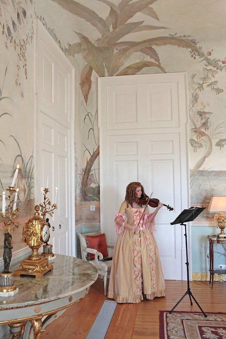 Woman in antique dress playing violin in corner of salon with painted walls