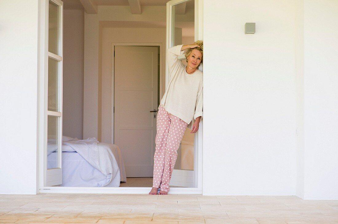 Older woman in pyjamas leaning on terrace door leading to bedroom