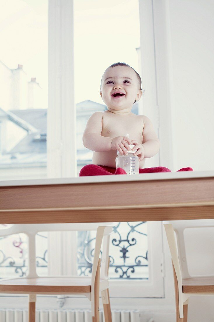Laughing baby with its bottle sitting on a table