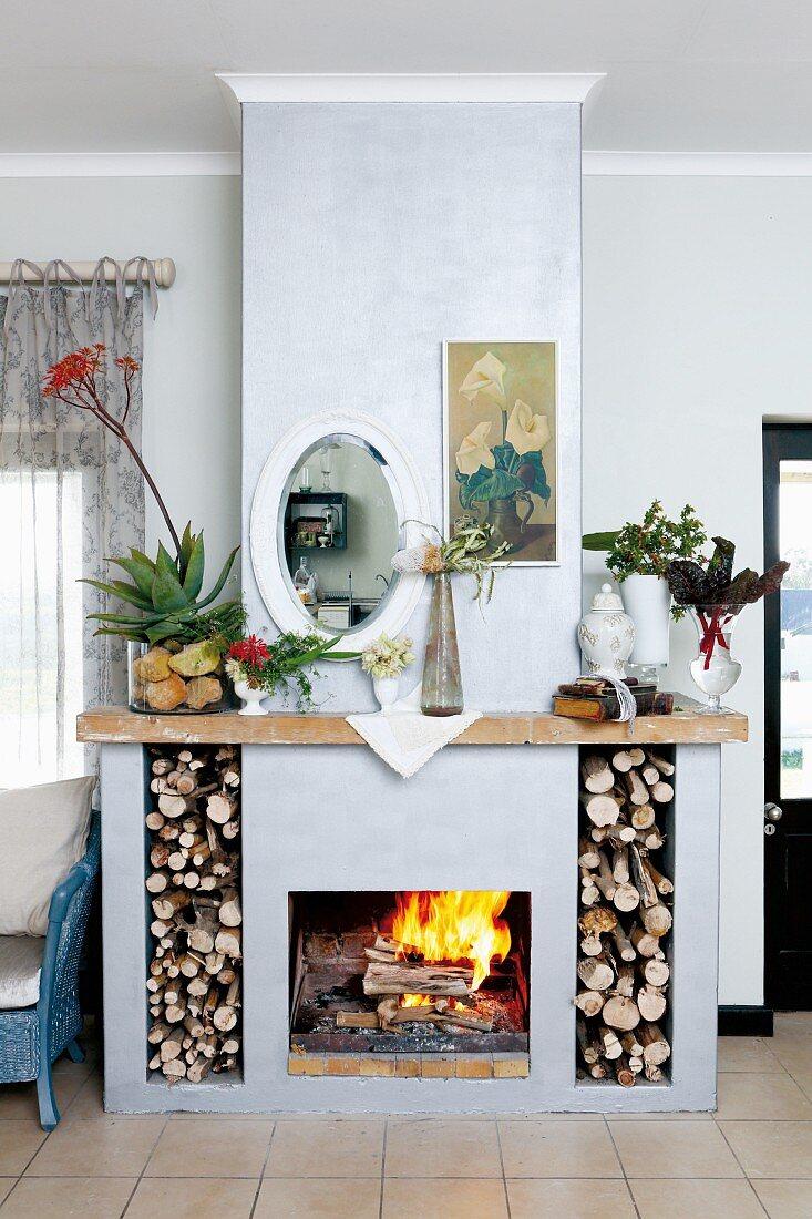 Offener Kamin mit Brennholzfächern und Kaminsims mit Aloe und Gartenpflanzen, darüber Wandspiegel und Blumenbild