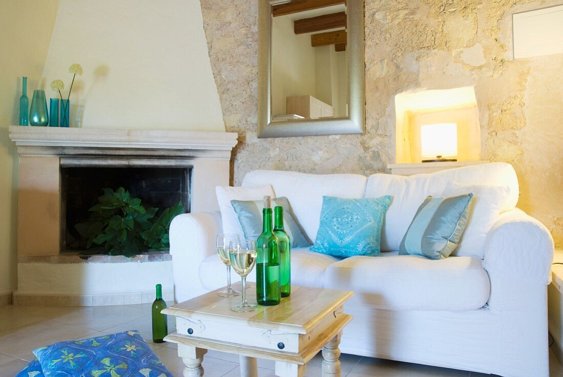 Sofa with white upholstery next to fireplace in Mediterranean living room with stone walls