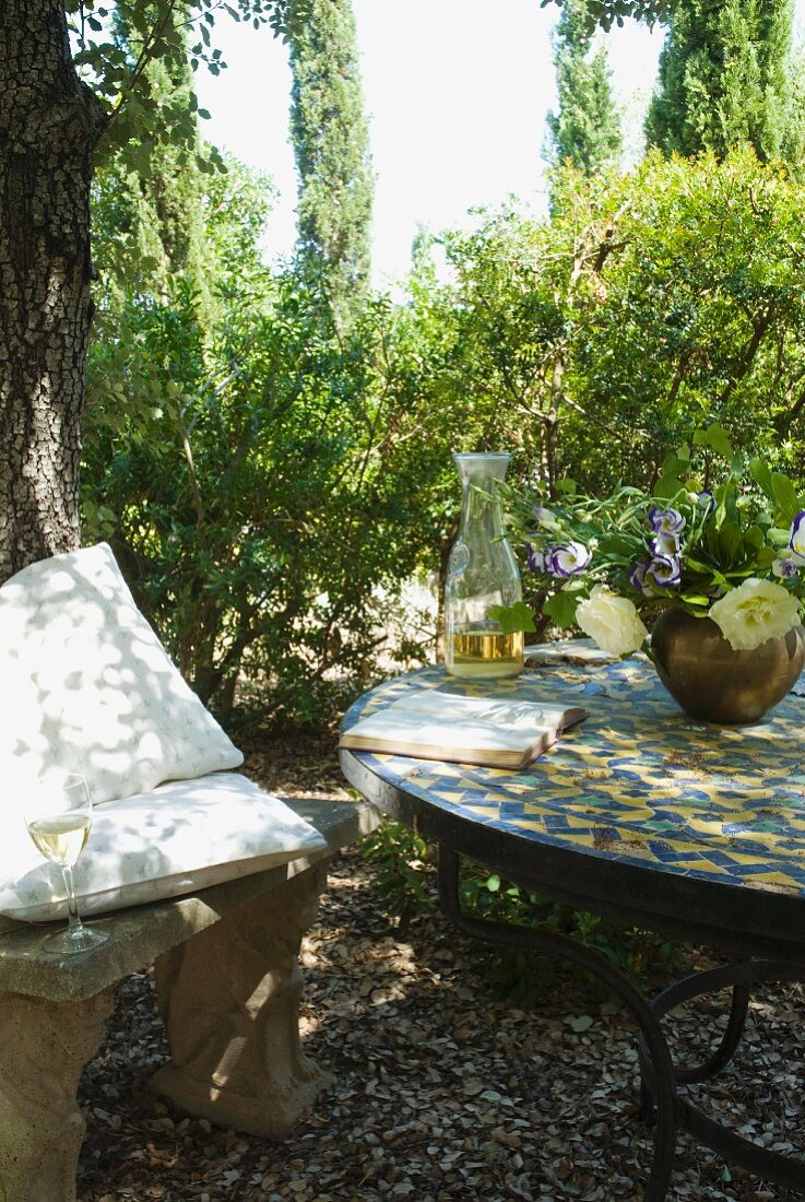 Wine glass and cushions on antique stone bench and book on tiled table