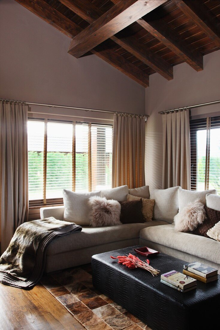 Cozy, fur look accessories on a bright, corner sofa and black ottoman under an impressive wood beam ceiling