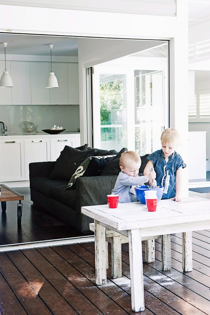Children baking at table on roofed veranda