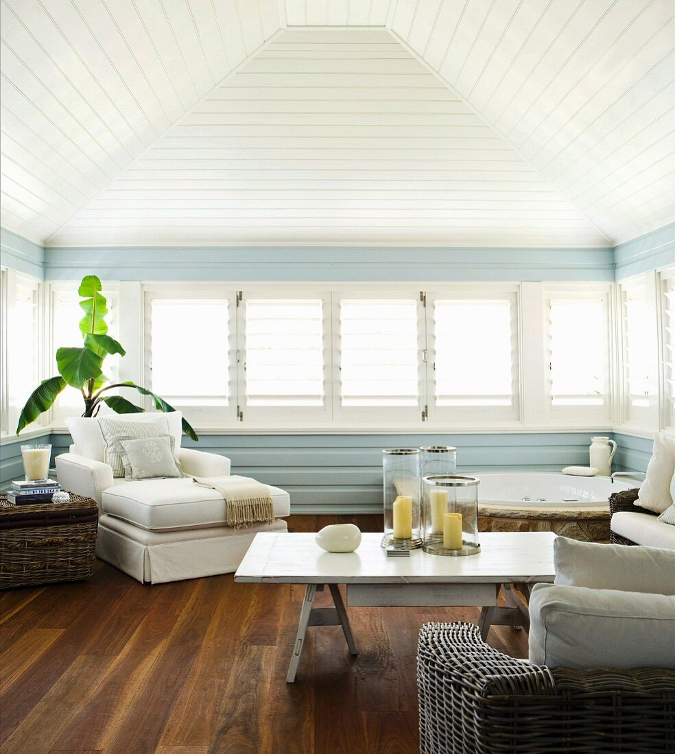 Spa area with corner bathtub and white upholstered furniture in pastel-blue interior with long bank of windows