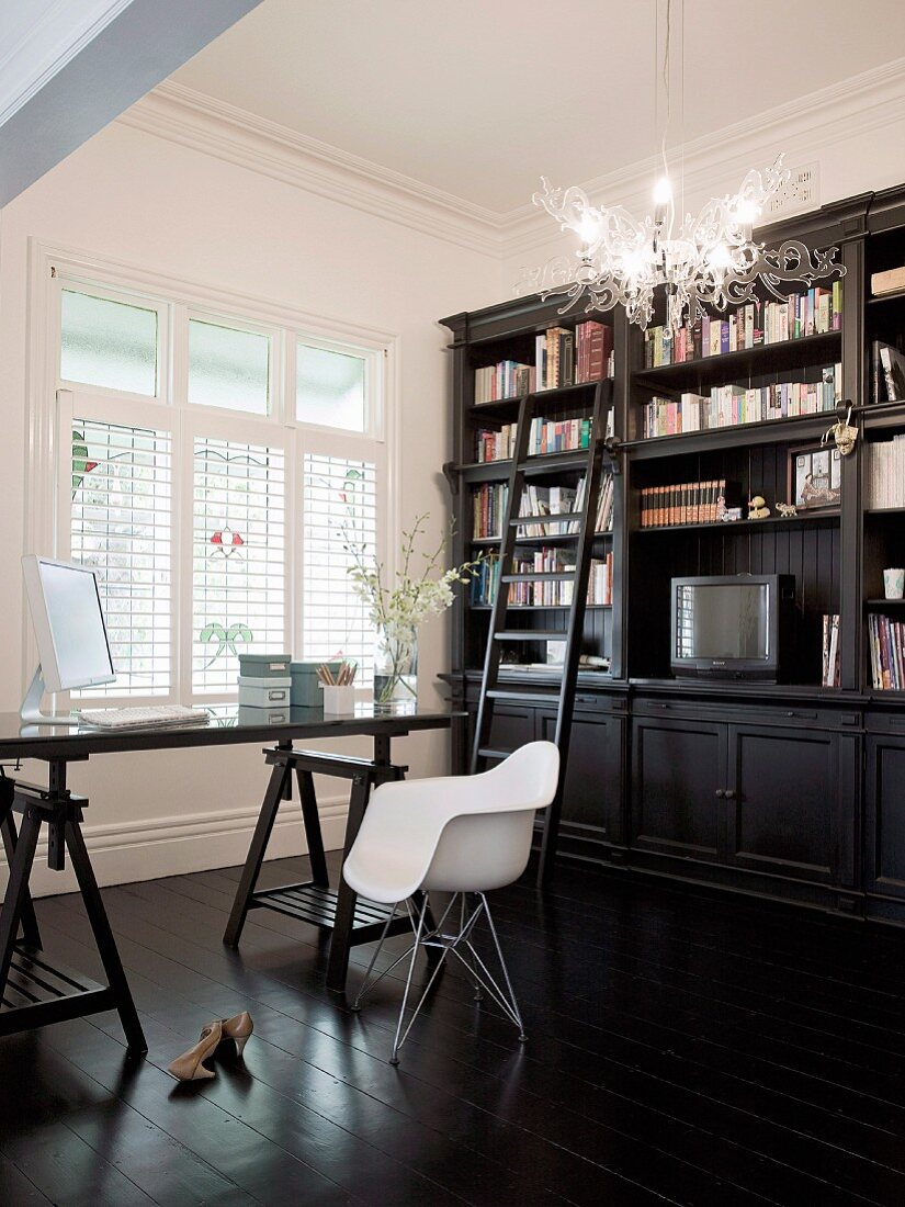 Dark furniture in study - desk on trestles, classic chair and country-house bookcase behind plexiglass lamp