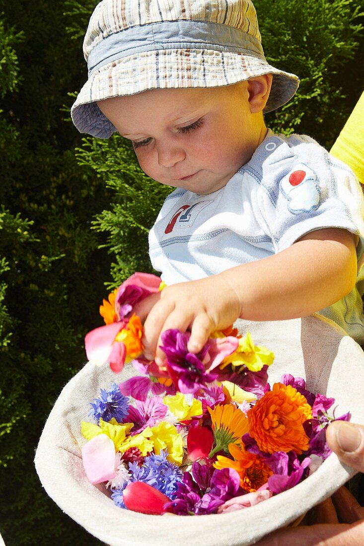 Baby playing with basket of flowers