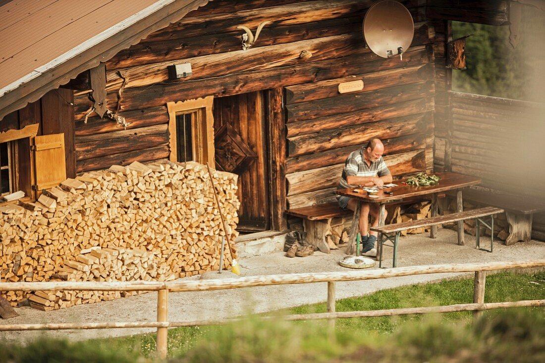Mann liest am Tisch vor einer Almhütte