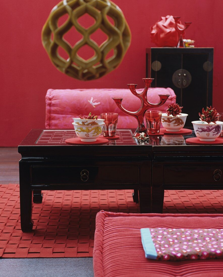 A black Asian tea table laid with bowls, on a red rug with a red wall to the rear