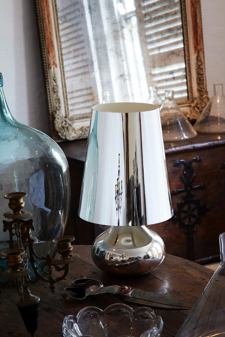 Vintage candlestick, garden shears, silver table lamp and demijohn on wooden table