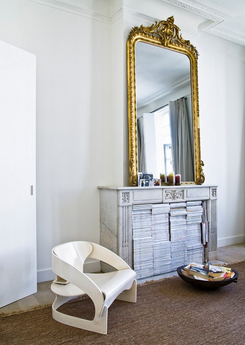 Collection of magazines in disused open fireplace, gilt-framed mirror and modern, retro-style chair