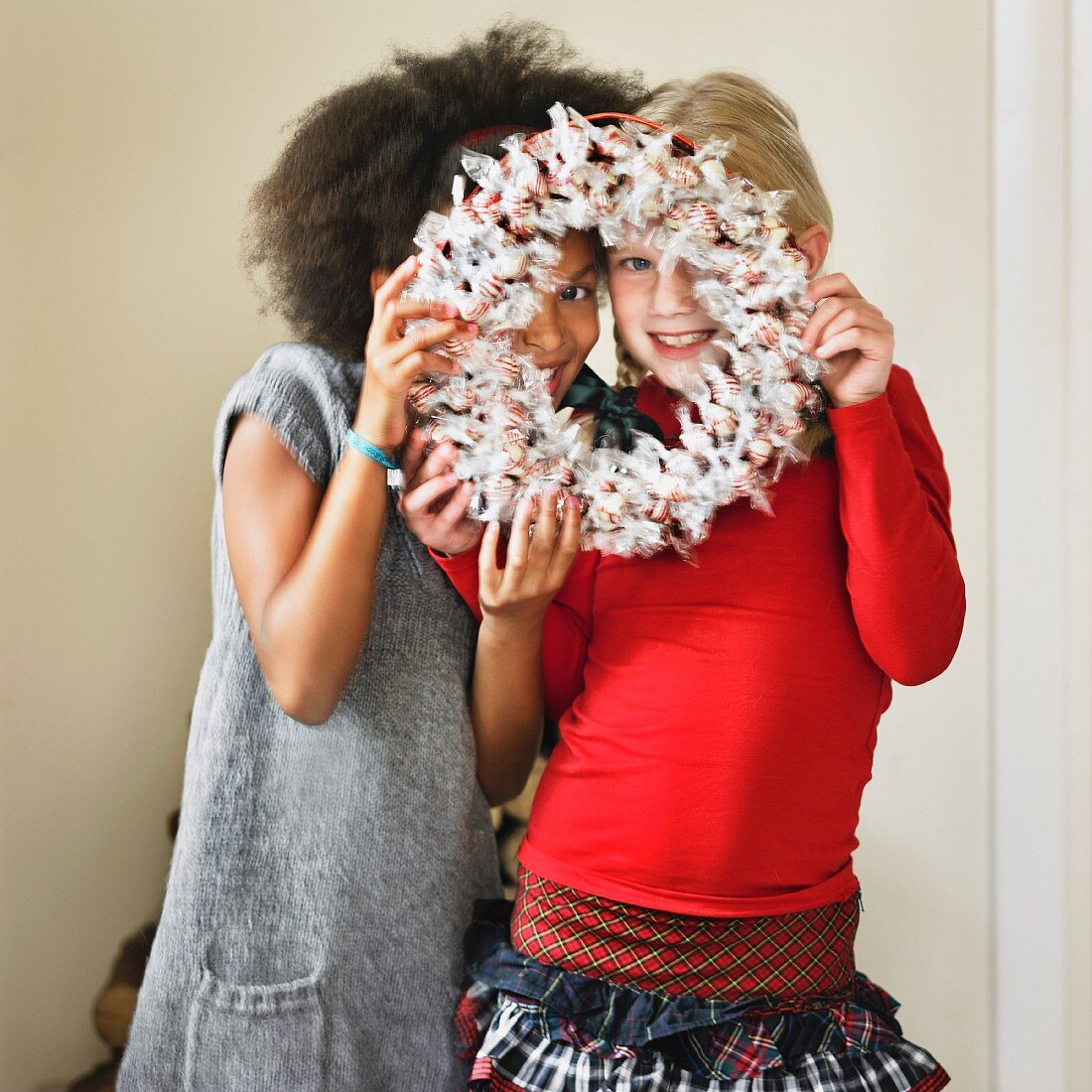 Girls looking through a Christmas wreath