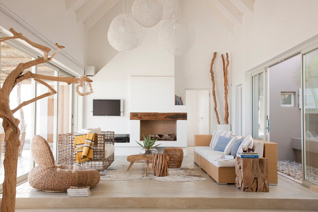 Bright interior with sloping roof, unusual furnishings made from natural materials and two glass walls