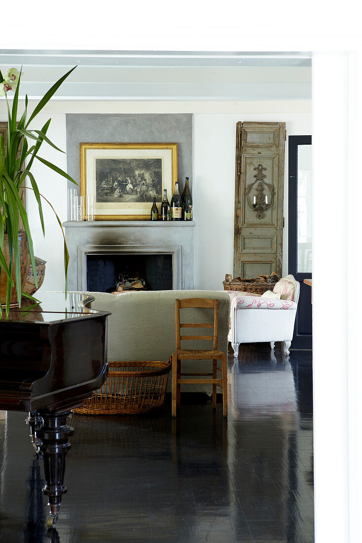 Comfortable country-house ambiance with sofa set in front of fireplace and classic grand piano on polished, black wooden floor