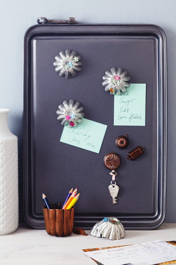 Baking tray used as magnet pinboard with magnets made from small cake moulds & dolls house cake moulds