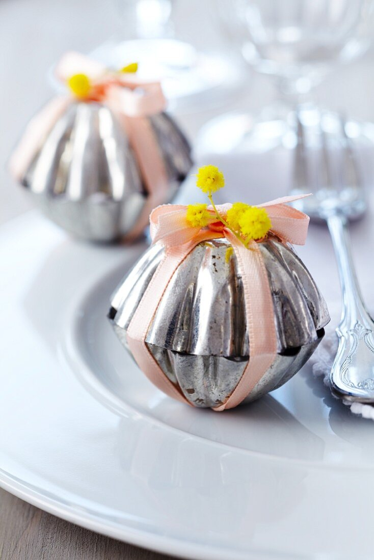 Small cake moulds decorated with flowers & satin ribbons used as packaging for guest favours