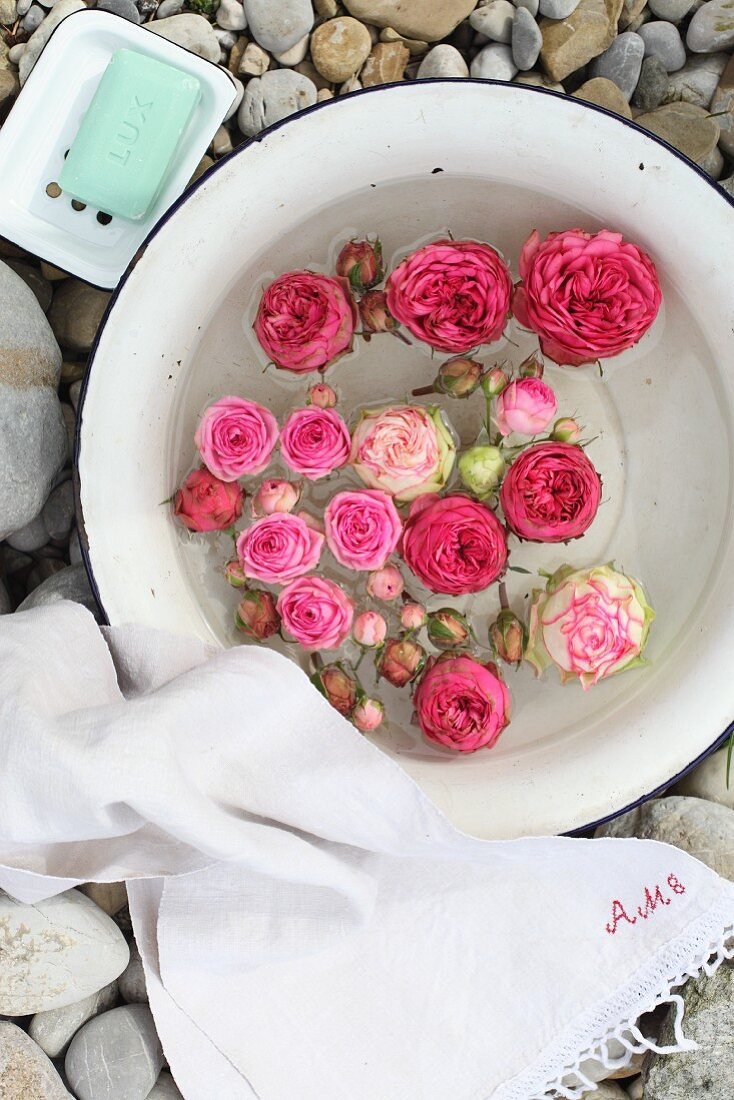 Roses floating in enamel bowl arranged with white linen towel and soap dish on gravel floor