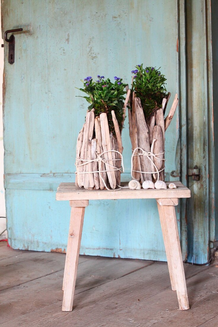 Original planters made from tied bundles of pale driftwood on wooden stool in front of vintage door