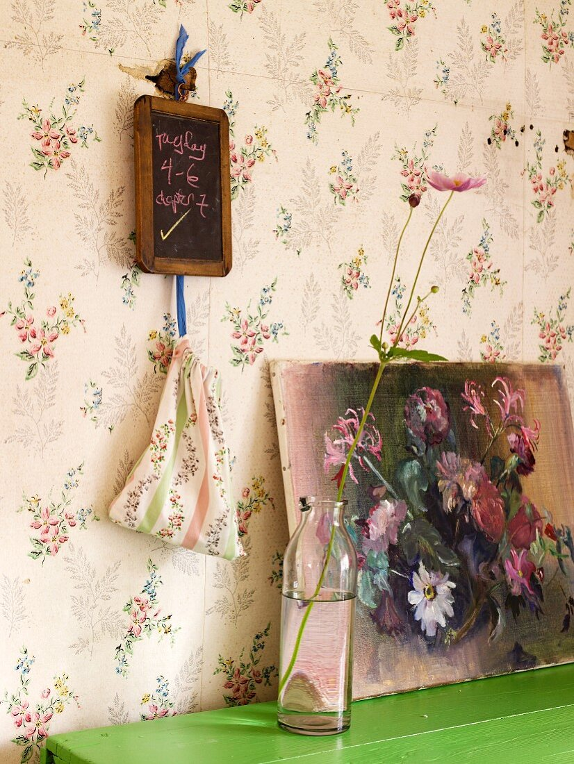 A vase holding a flower, and a picture of a still life featuring flowers, on a green tabletop; a small blackboard on a wall papered with a flower pattern