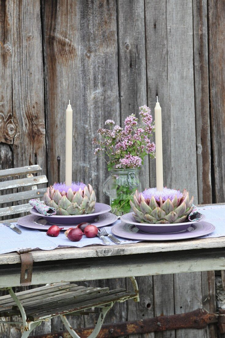 Place settings with candles in artichoke flowers and flowering marjoram in preserving jar