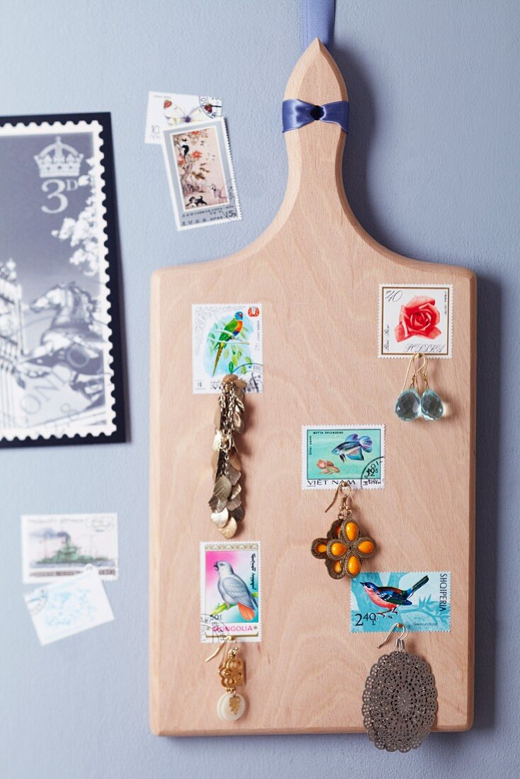 Chopping board decorated with postage stamps and used as a jewellery rack