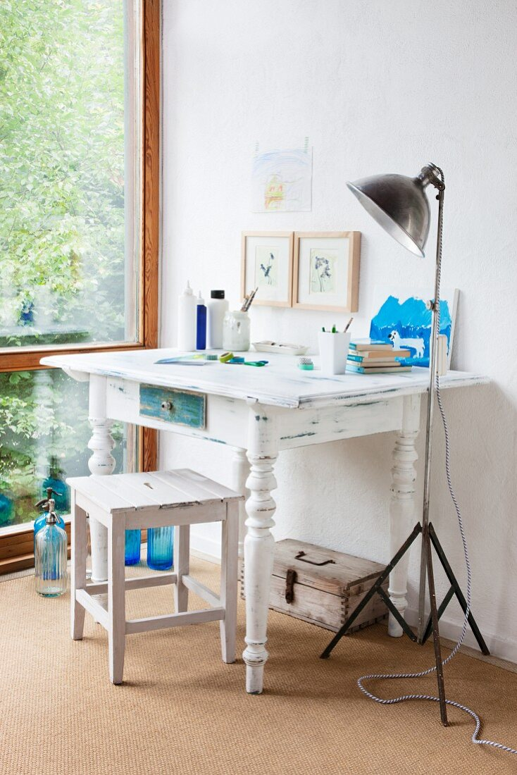 White-painted wooden table with turned legs and vintage-look stool next to retro, metal standard lamp in corner