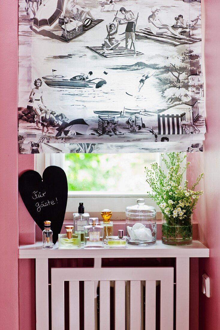 Roman blind with black and white print at bathroom window and bottles of perfumes for guests