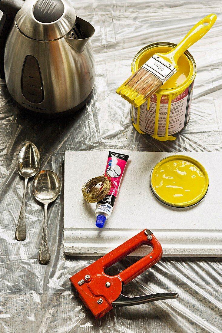 Gelbe Farbdose mit Pinsel, Tacker, weiße Sockelleist und Esslöffel