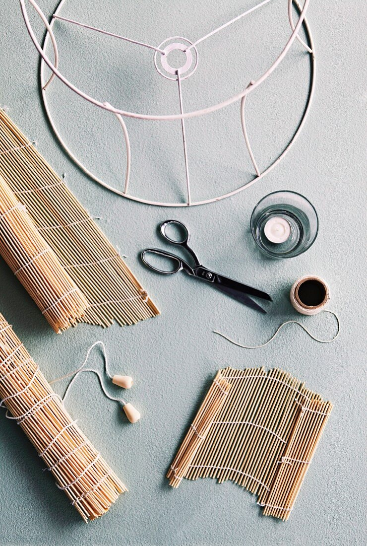 Bamboo place mat, scissors, tealight and metal lampshade frame