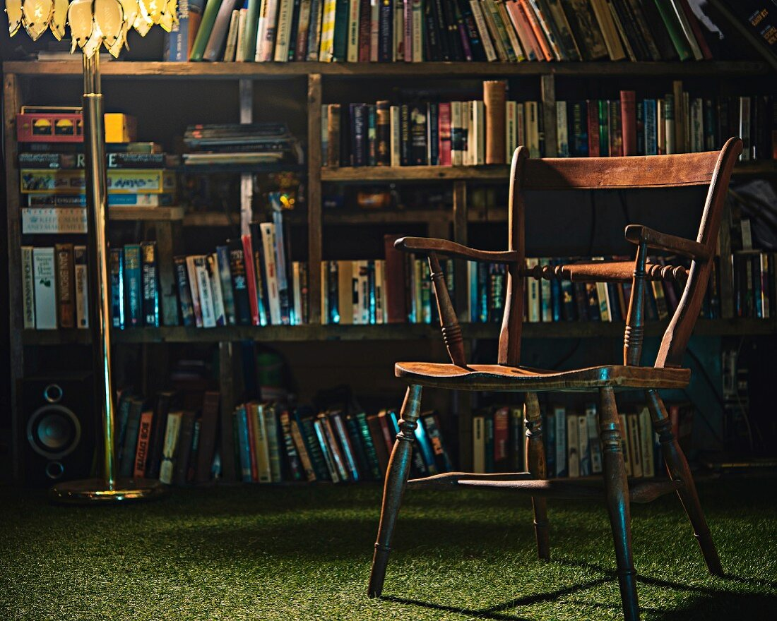 Old wooden chair & standard lamp in front of bookcase