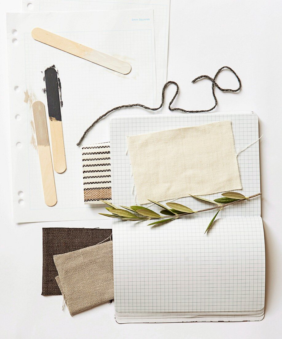 Fabric swatches in earthy tones, olive sprig, length of wool and paint samples on wooden lolly sticks