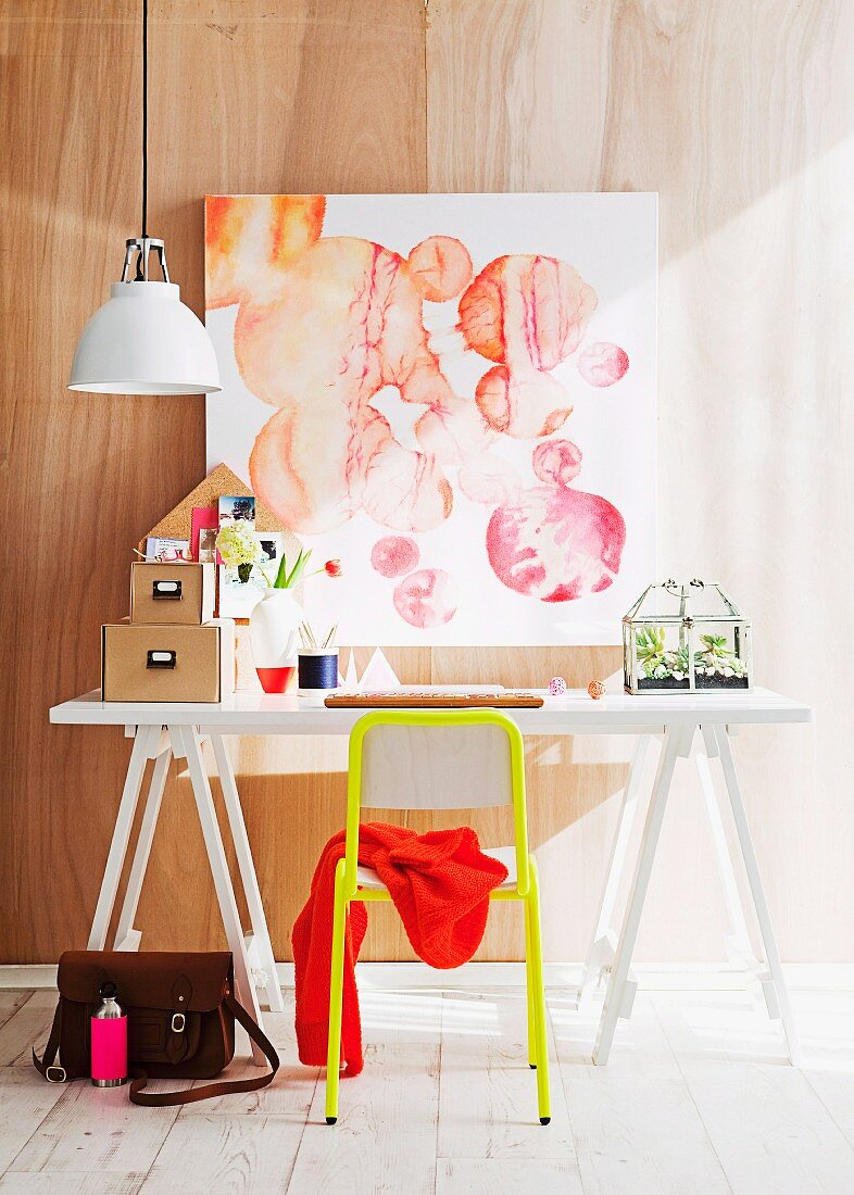 White desk and yellow chair below abstract watercolour on wall