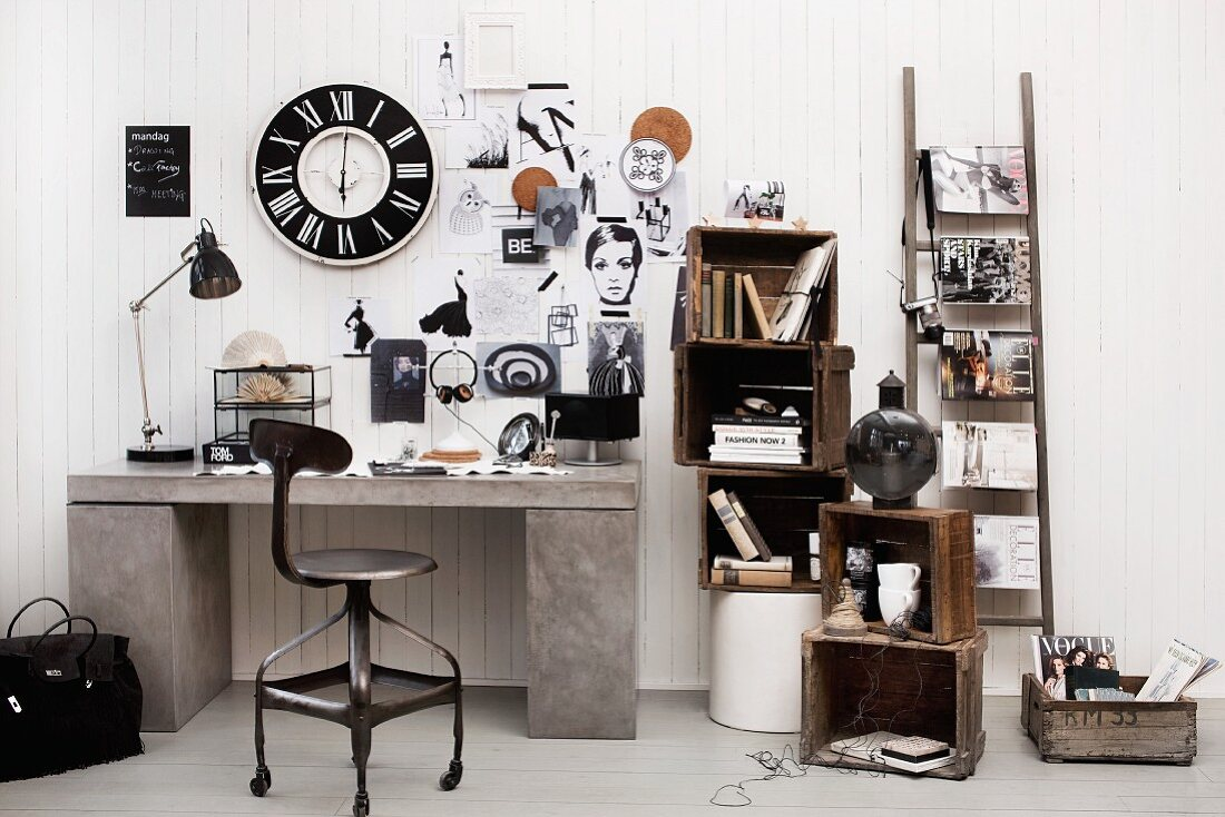 Black and white vintage decor, wooden crates, ladder and wall clock above concrete-effect desk; wood panelling used as pinboard