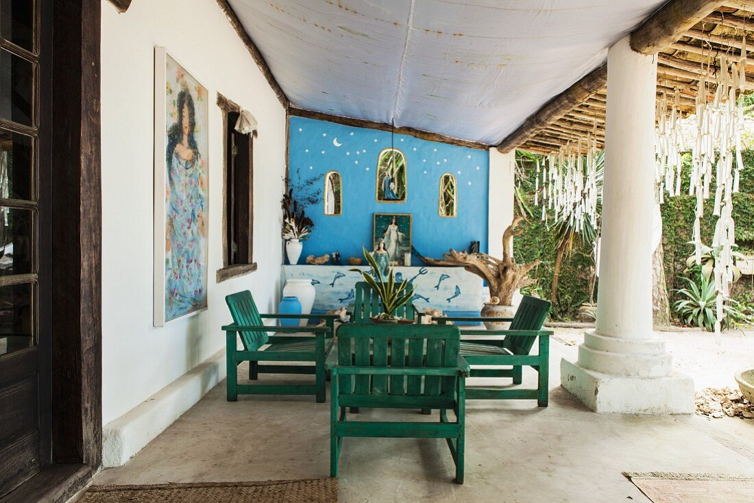 Wooden furniture on roofed terrace of Brazilian beach house with enormous supporting column; pictures of sea goddess Lemanja and altar wall in background