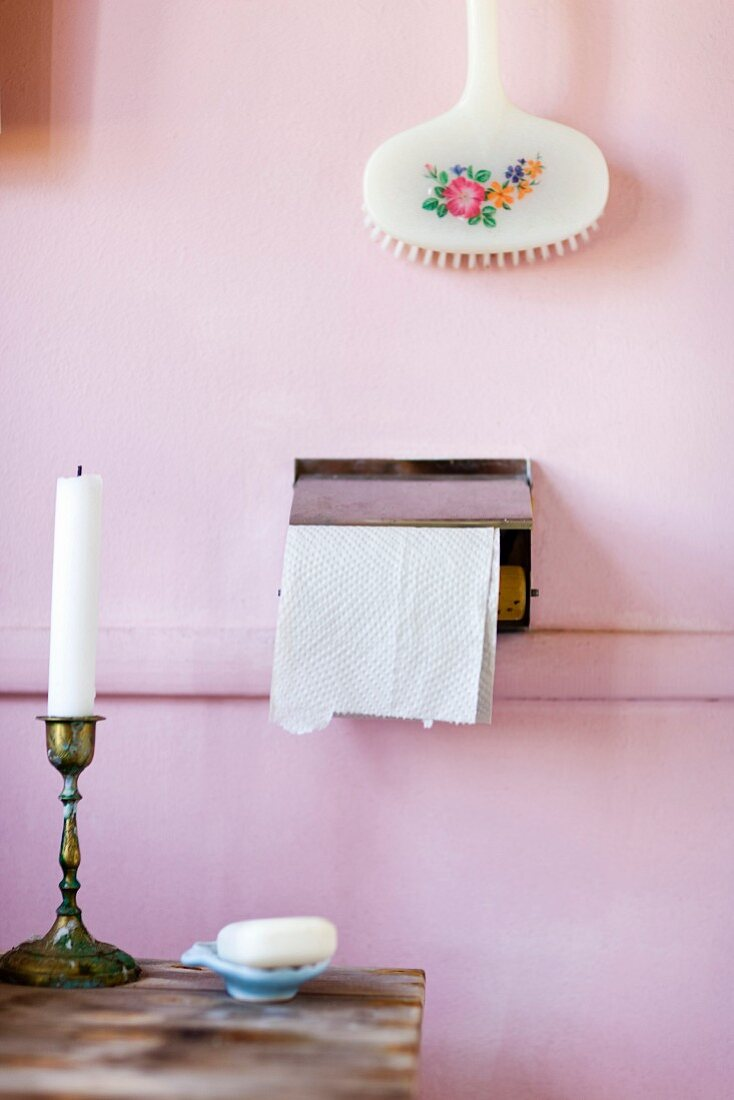 Candlestick on wooden table and floral bath brush above toilet roll holder on pink-painted wall