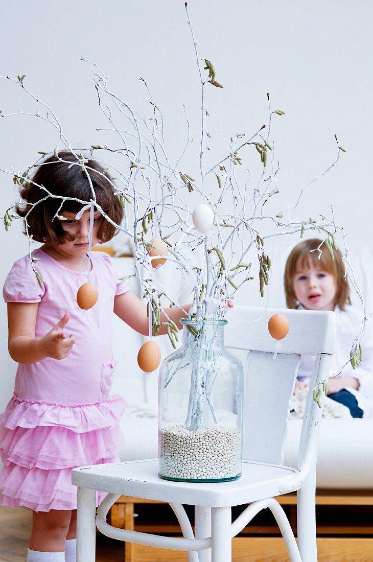 Little girls and Easter arrangement in large glass vase