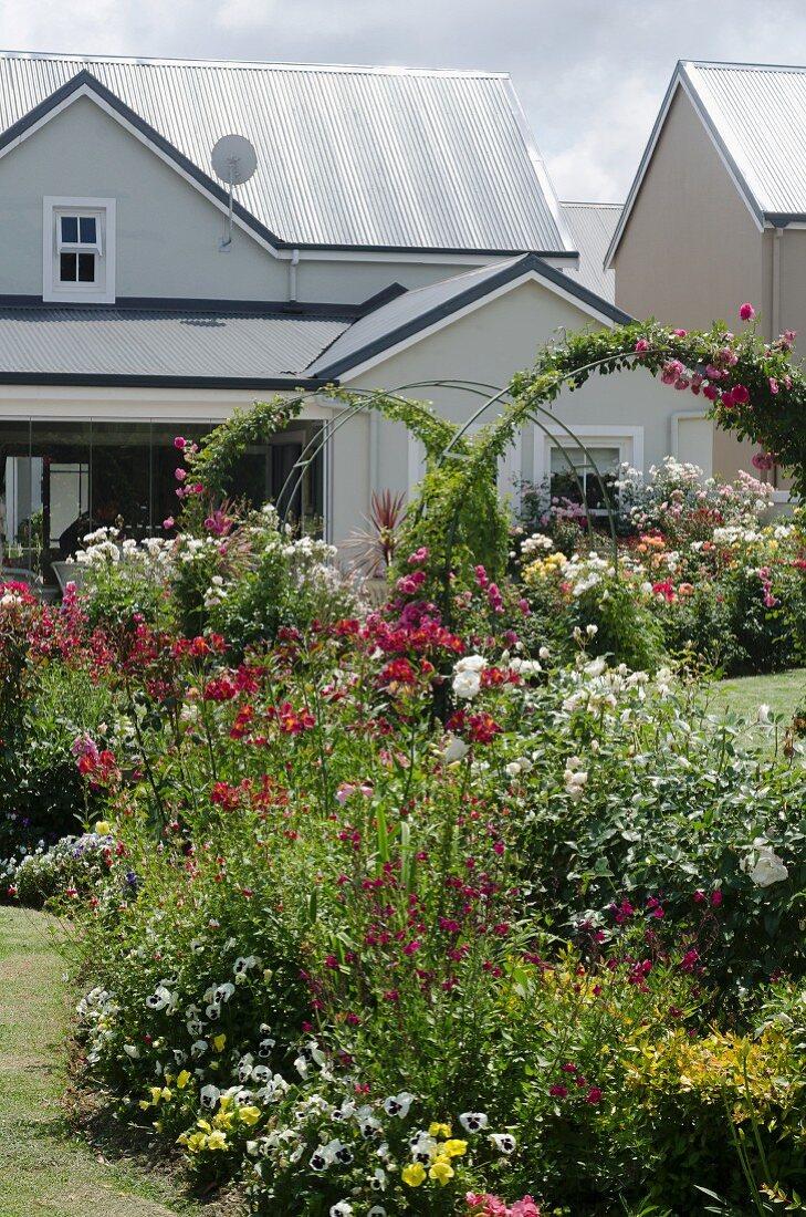 Farbenfroh blühende Blumenrabatte vor grau-weißem Wohnhaus
