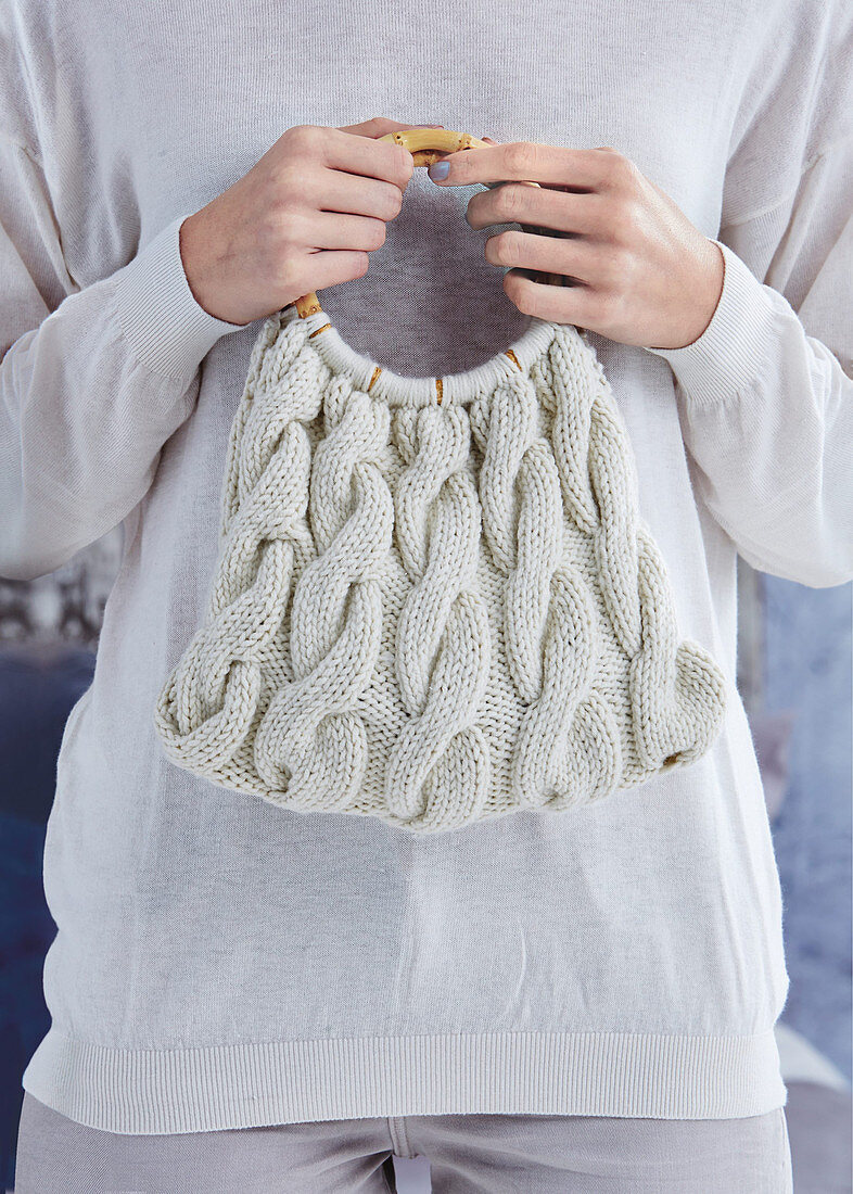 Hand-knitted bag held in woman's hands