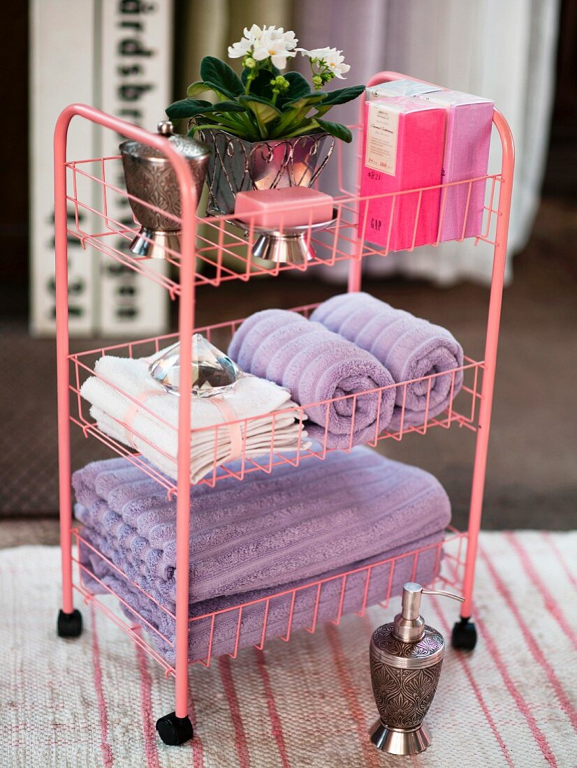 Pink bathroom trolley for storing towels and toiletries