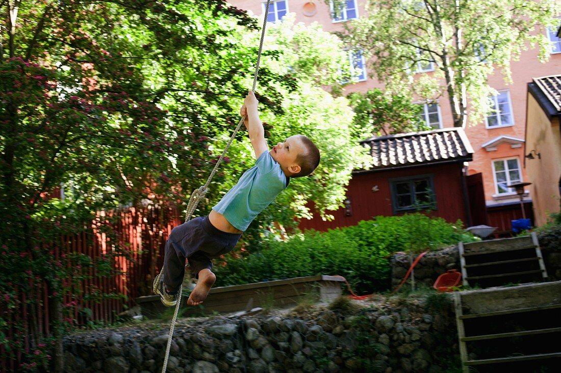 Kleiner Junge klettert an Seil hoch