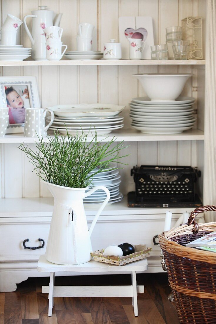 Floral crockery, photo of child and old typewriter on open shelves behind bouquet in enamel jug and Easter eggs